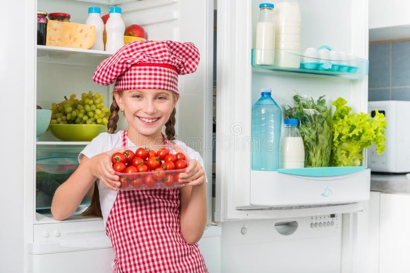 Mali kucbarscy mienie pomidory zbliżają fridge fotografia stock