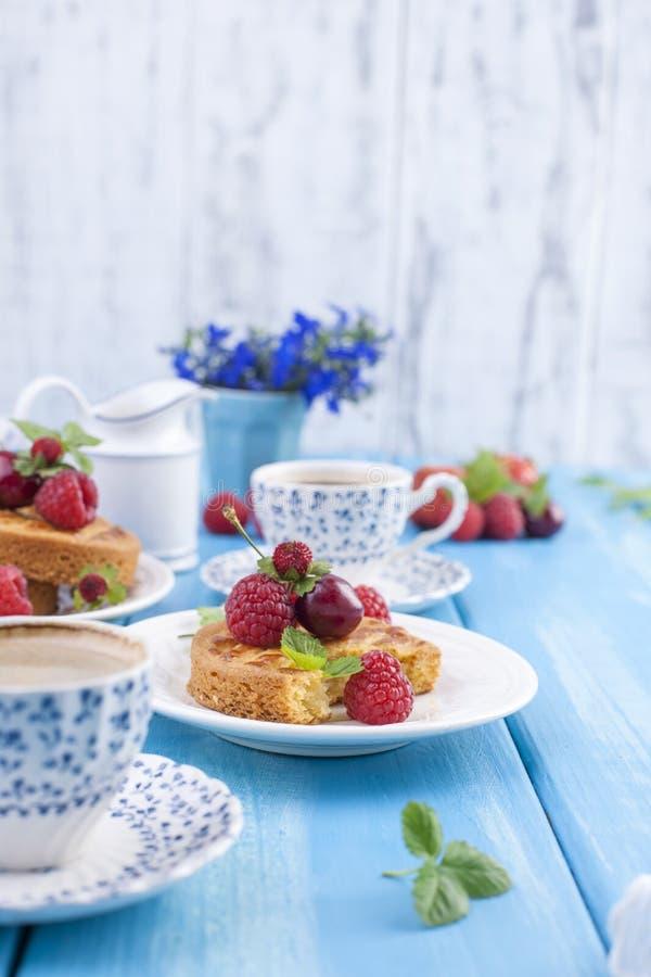 Mali kulebiaki z jagodami, truskawkami i wiśniami, Wyśmienicie słodki śniadanie i fragrant kawa na błękitnym drewnianym tle, zdjęcie royalty free
