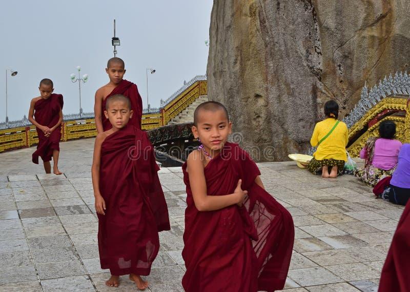 Mali mnisi buddyjscy przechodzi obok z rozochoconym spojrzeniem przy Złotą skałą w Mon stanie, Myanmar fotografia stock
