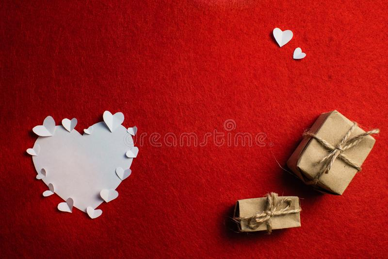 Mali papierowi serca okrążają dużego białego serce i dwa prezenta pudełka na czerwonym tle i zdjęcie royalty free