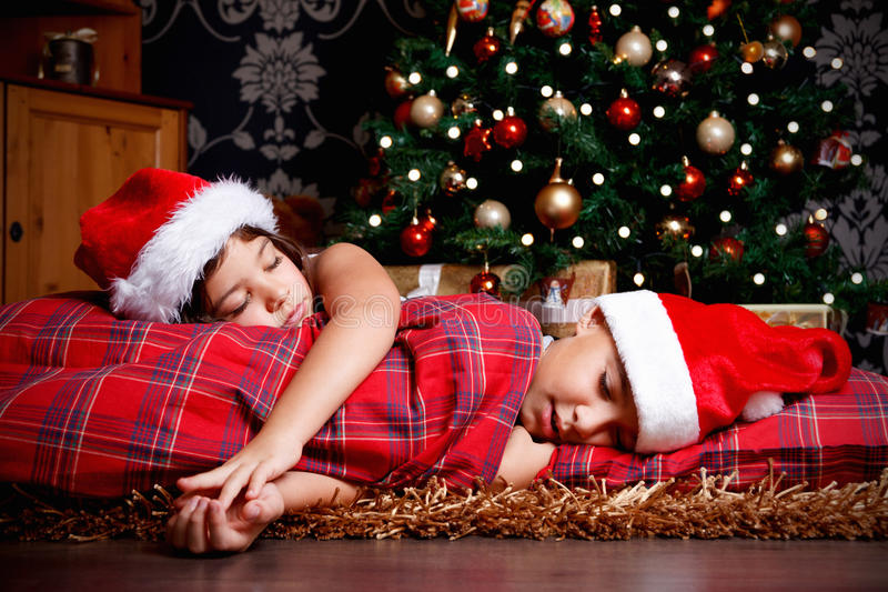 Mali rodzeństwa uśpeni podczas gdy czekający prezent fotografia stock
