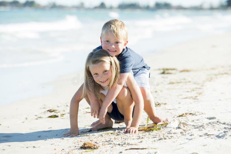 Mali uroczy i słodcy rodzeństwa bawić się wpólnie w piasek plaży z małym bratem ściska jego pięknego blond młodego siostrzanego e obrazy stock