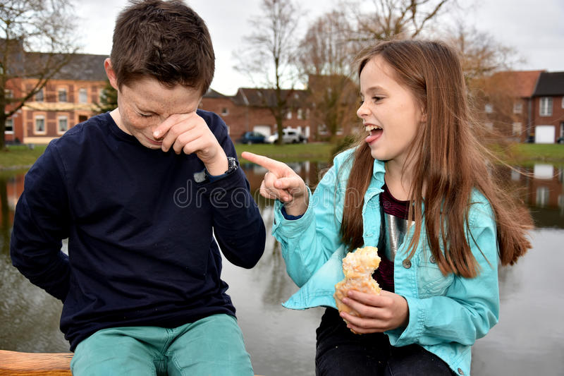 Malicious joy. Girl needles her brother because she has pastry and he has nothing stock photography