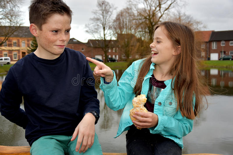 Malicious joy. Girl needles her brother because she has pastry and he has nothing royalty free stock photos