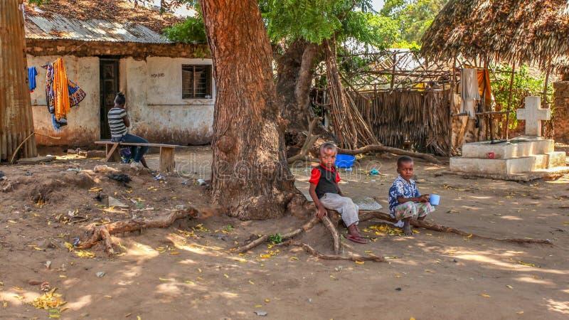Malindi, Kenia - 6. April 2015: Unbekannte lokale Kinder, die auf Baumwurzel vor ihrem Haus sitzen Lebensbedingungen in diesem Be lizenzfreies stockbild