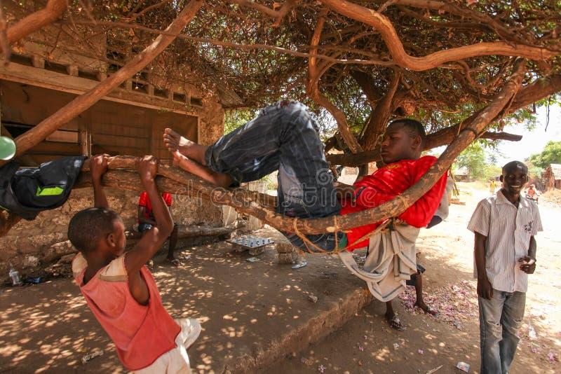 Malindi Kenya - April 06, 2015: Okänd kal footed lokal afrikansk pojke som kopplar av på trädfilialer och den enkla hängmattan fr royaltyfria bilder