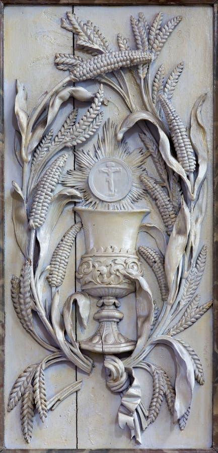Malines - il sollievo scolpito del cappuccio come simbolo del eucharist e del corpo di Jesus Christ in chiesa la nostra signora a immagine stock