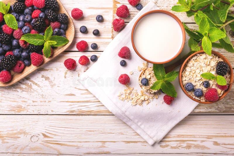 Malinka, czernica i czarna jagoda, oatmeal śniadanie z mlekiem zdjęcia royalty free