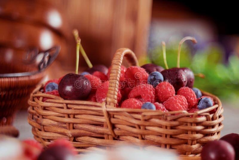 Malinki i czarne jagody w koszu z słodkiej wiśni latem i zdrową karmową selekcyjną ostrością zdjęcia stock