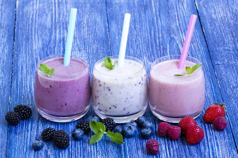Malinki, truskawki i czarnej jagody smoothie na błękitnym drewnianym tle, Milkshake z świeżymi jagodami jagodowy jogurt z obraz royalty free
