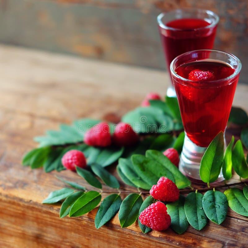 Malinowy owocowy ajerkoniak w dwa strzałów szkłach z jagodami i gre zdjęcia royalty free