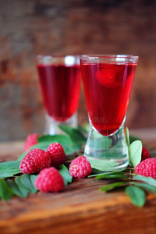 Malinowy owocowy ajerkoniak w dwa strzałów szkłach z jagodami i gre obrazy stock