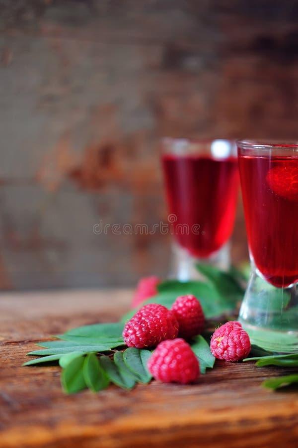 Malinowy owocowy ajerkoniak w dwa strzałów szkłach z jagodami i gre zdjęcie royalty free