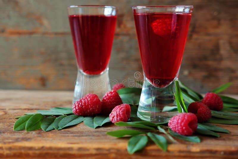 Malinowy owocowy ajerkoniak w dwa strzałów szkłach z jagodami i gre zdjęcie stock
