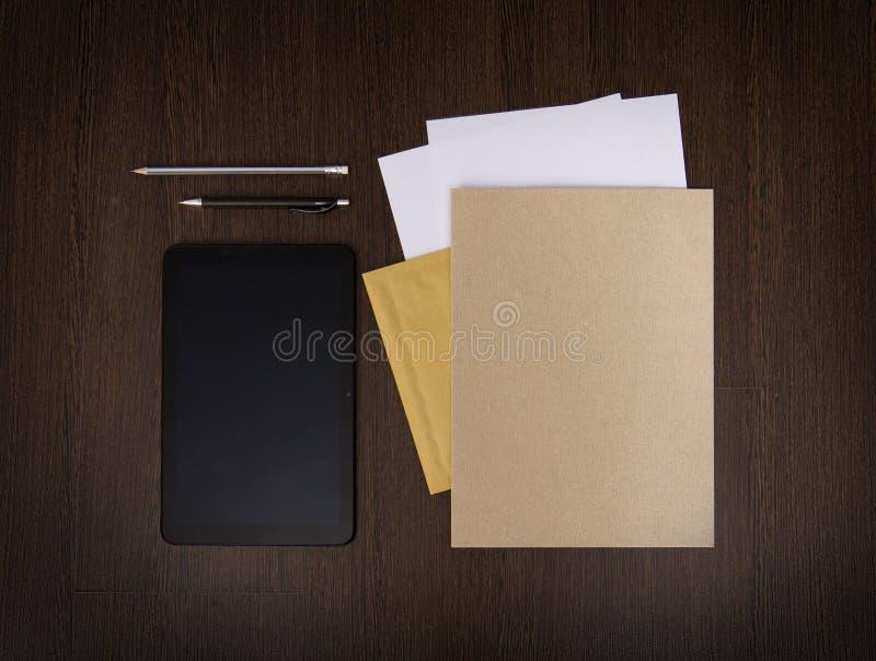 Mall för modellaffärsmärke på mörk träbakgrund Uppsättning av brevpapper med den digitala minnestavlan, återanvänd mapp, papper royaltyfri bild