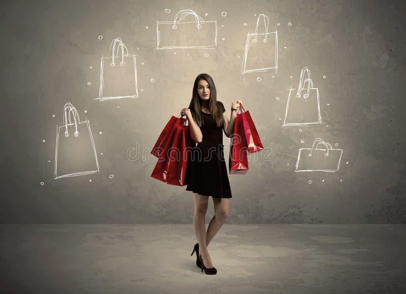 Malldame mit gezogenen Einkaufstaschen auf Wand stockbild