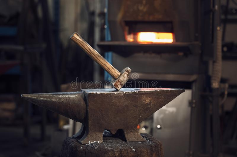 Mallet on an anvil in front of a furnace stock image