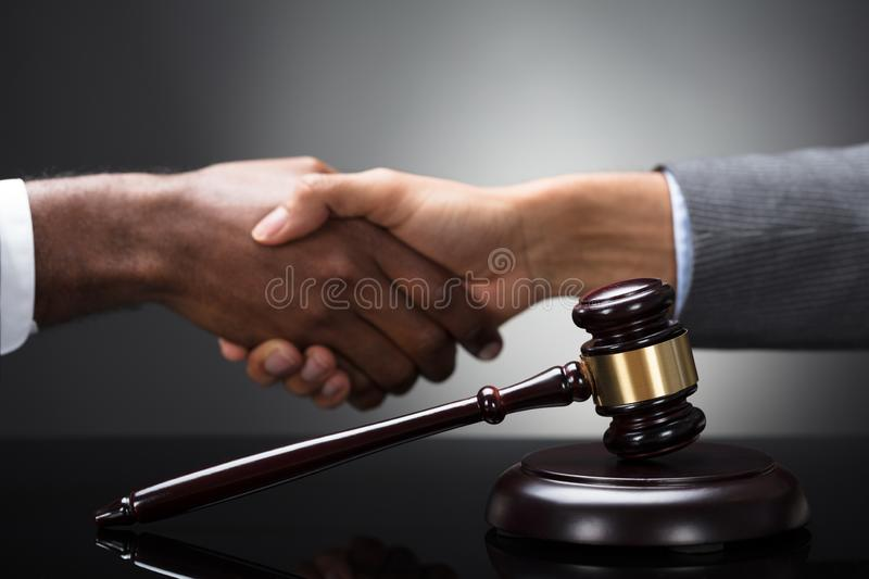Mallet And Gavel In Front Of Two Businesspeople Shaking Hands royalty free stock images