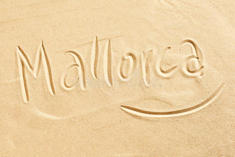 Mallorca handgeschrieben im goldenen Strandsand stockfotos