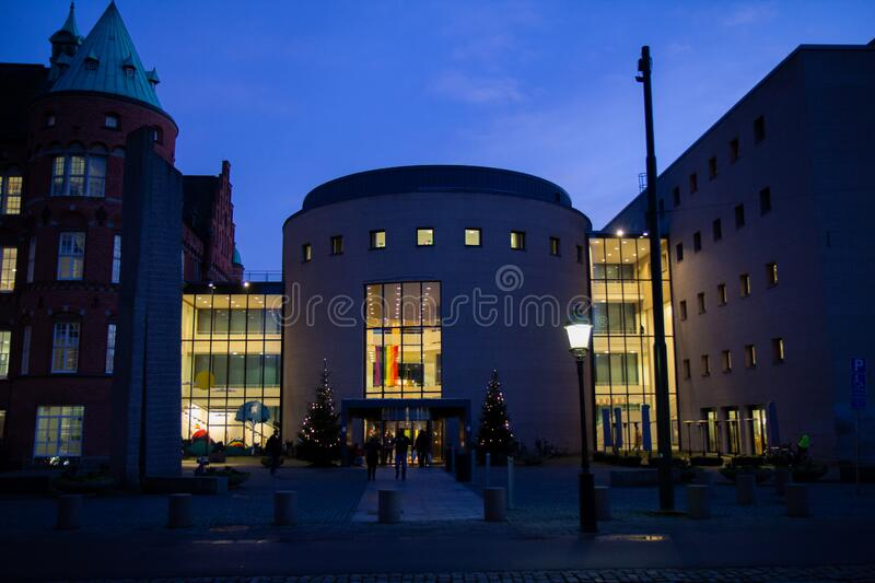 Malmö, Sweden - December 21, 2019: The main entrance to the city library is placed in a large round concrete building that. Connects the old and the new stock photo