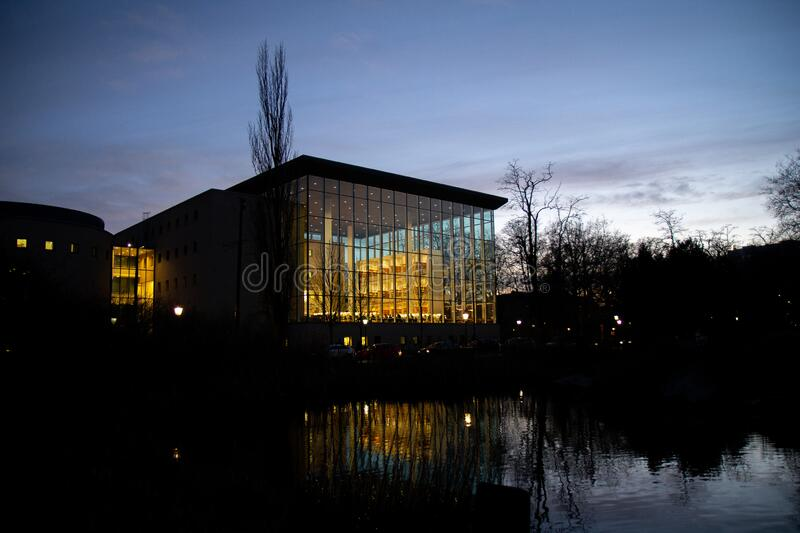 Malmö, Sweden - December 21, 2019: The modern glass facade that makes up a big part of the city library, placed in a public park. Here seen during a cold royalty free stock image