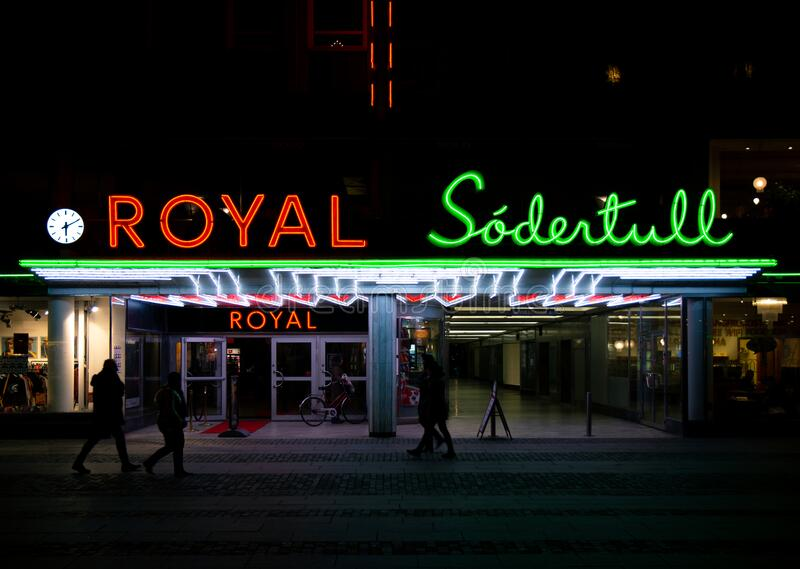 Malmö, Sweden - December 1, 2019: People are walking by the neon sign decorated entrance to the cinema Royal owned by the movie. Company Filmstaden royalty free stock photos