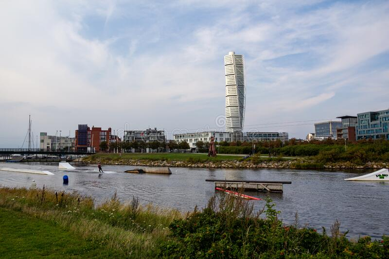 Malmö, Sweden - September 1, 2019: A person is practicing wake boarding in the canal close to the skyscraper Turning Torso, seen. In the distance stock image