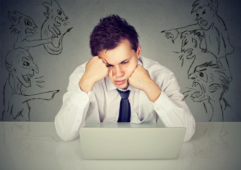 Malos hombres malvados que señalan en el individuo subrayado que se sienta en la tabla con el ordenador portátil imagen de archivo