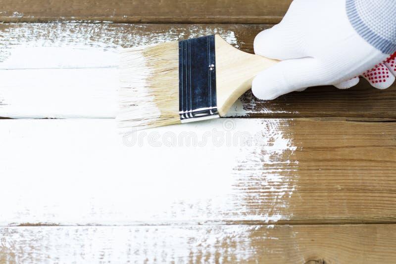 Malować drewnianą powierzchnię z białą farbą, gloved ręka trzyma farby muśnięcie zdjęcia stock