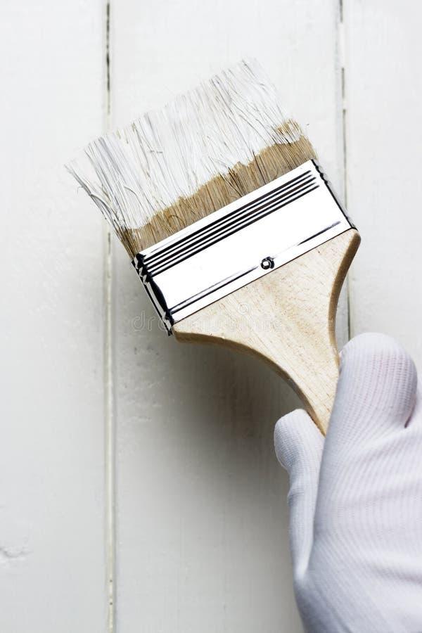 Malować drewnianą powierzchnię z białą farbą, gloved ręka trzyma farby muśnięcie fotografia royalty free