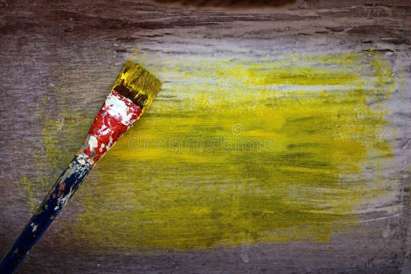 Malować drewnianego tło kolor żółtego Szczotkarska rękojeść splattered z wiele kolorami farba od częstego używa obrazy royalty free