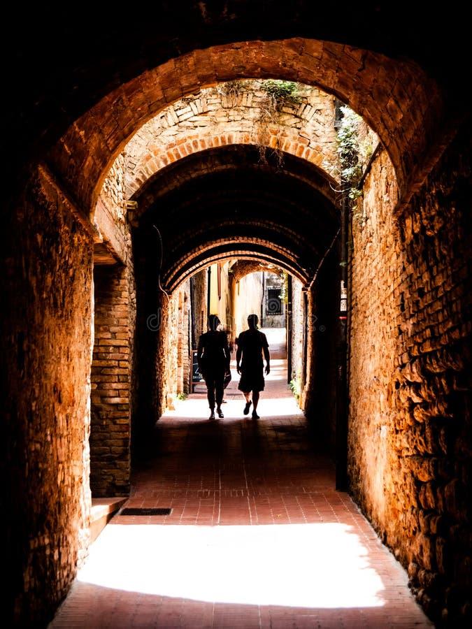 Malownicza średniowieczna wąska ulica San Gimignano stary miasteczko z dwa osob sylwetką w cieniu, Tuscany, Włochy fotografia royalty free