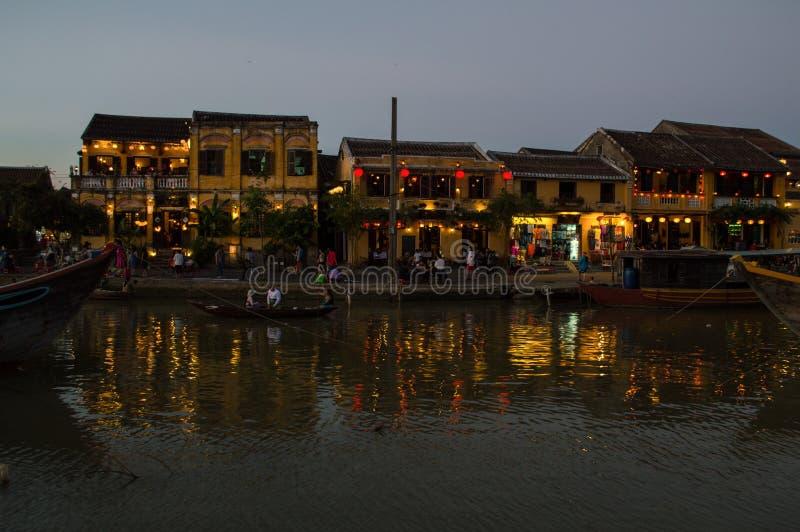 Malownicza ulica z lampionami, rzeką i łodziami w wieczór, fotografia royalty free