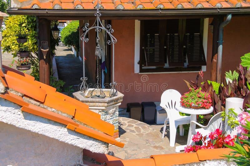 Malownicza well i kwiatu dekoracja blisko mieszkaniowego domu fotografia royalty free
