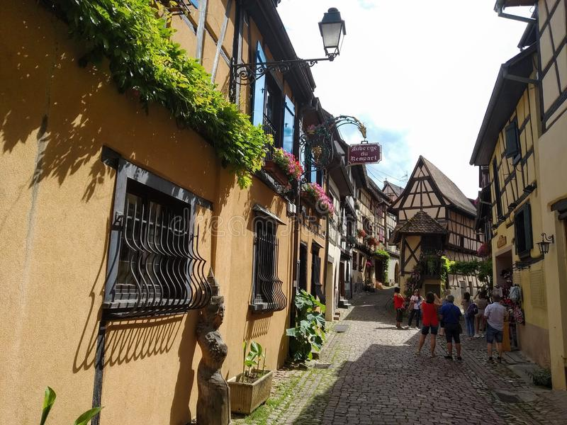 Malownicze aleje Eguisheim, tipical starzy domy dekorowali z kwiatami , Francja fotografia royalty free