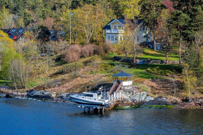 Malowniczej wiosny nabrzeżny krajobraz Sztokholm archipelag z nabrzeże dworem i małą motorową łodzią podnoszącymi nad - woda dale zdjęcie stock