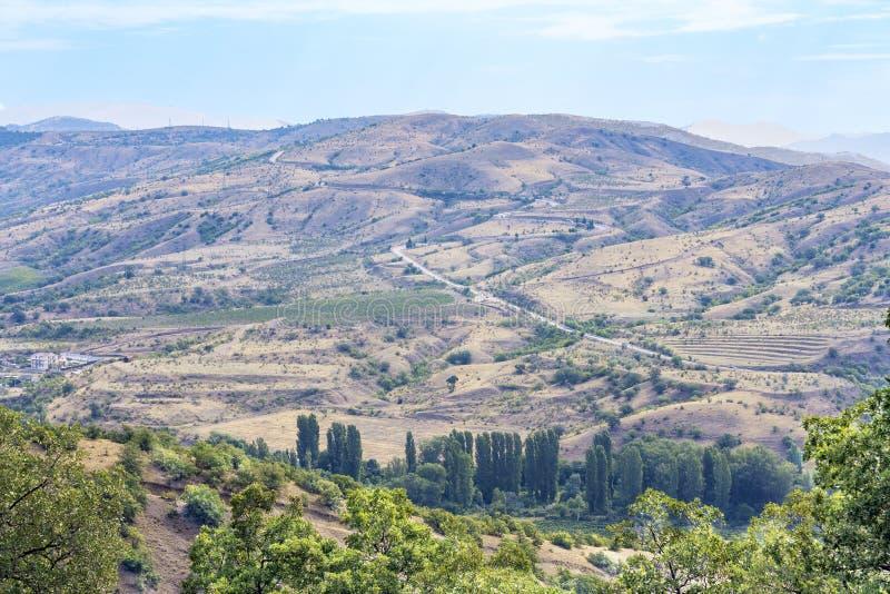 Malowniczy górzysty i górkowaty teren Crimea z drogą kłaść na nim obrazy royalty free