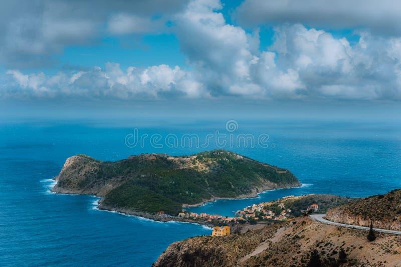 Malowniczy widok Assos wioska i błękitny morze trzymać na dystans Oszałamiająco cloudscape nad penincula Kefalonia wyspa, Grecja zdjęcia royalty free