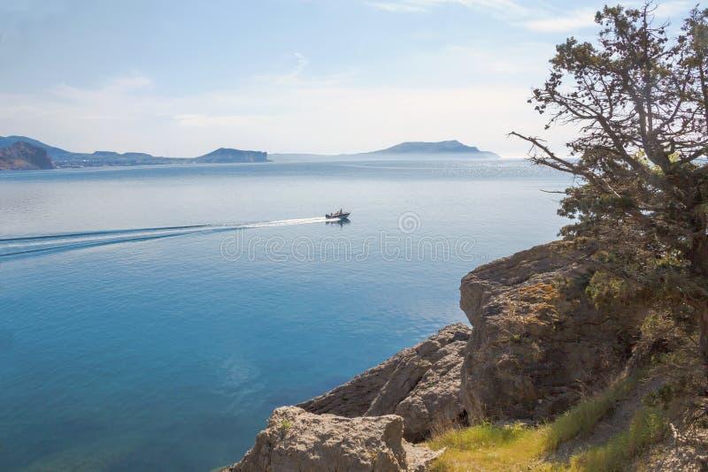 Malowniczy widok morze, góry na horyzoncie i motorowa łódź unosi się wzdłuż brzeg, zdjęcie royalty free