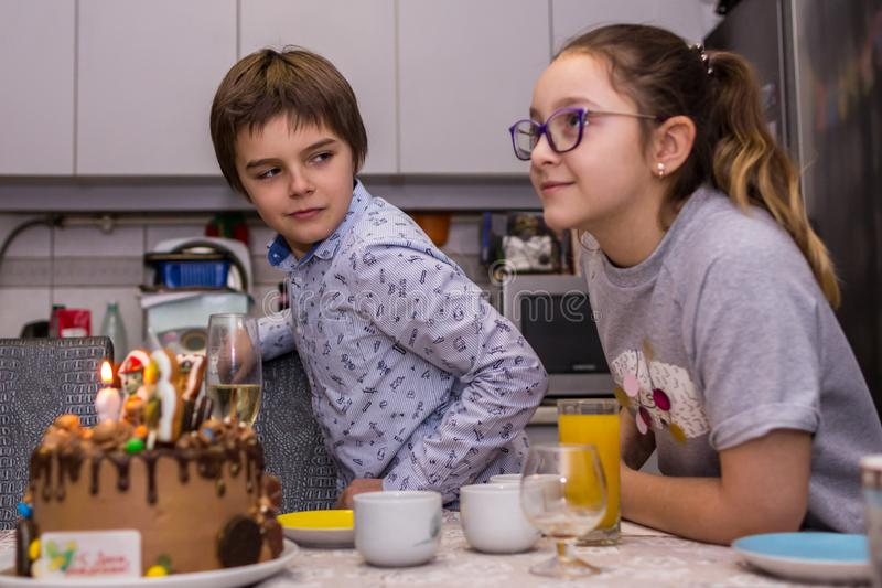 Happy birthday party at home. A brother and sister looking at the cake and going to blow out the candle on it. 2019.02.09, Maloyaros;avets, Russia. Happy stock photos