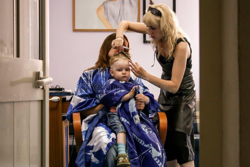 2010 06 12, Maloyaroslavets, Россия Парикмахер сушит волосы мальчика на салоне стоковые фотографии rf