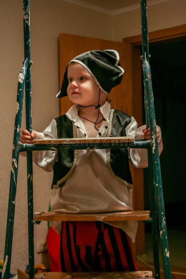 2010.11.28, Maloyaroslavets, Russia. A little boy wearing a pirate costume standing on ladder. royalty free stock photography