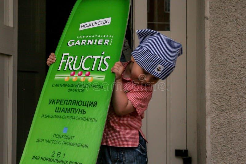 2010 06 12, Maloyaroslavets, Russia Un ragazzino in bandana che tiene un supporto di sciampo famoso fotografia stock