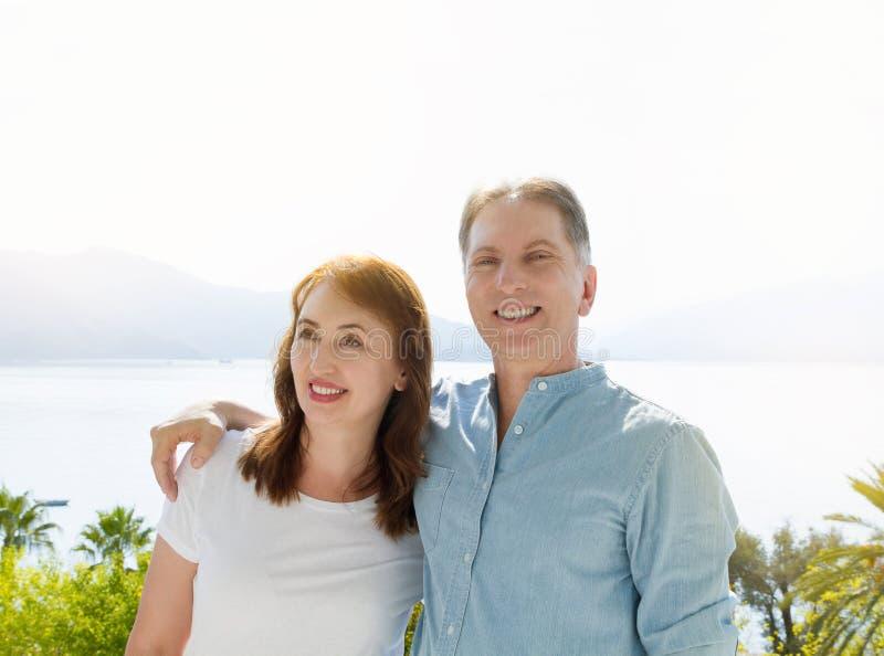 Malplaatje van de de zomer het witte t-shirt Gelukkig midden oud familiepaar bij vakantie Strand en vakantieconcept Exemplaarruim stock fotografie