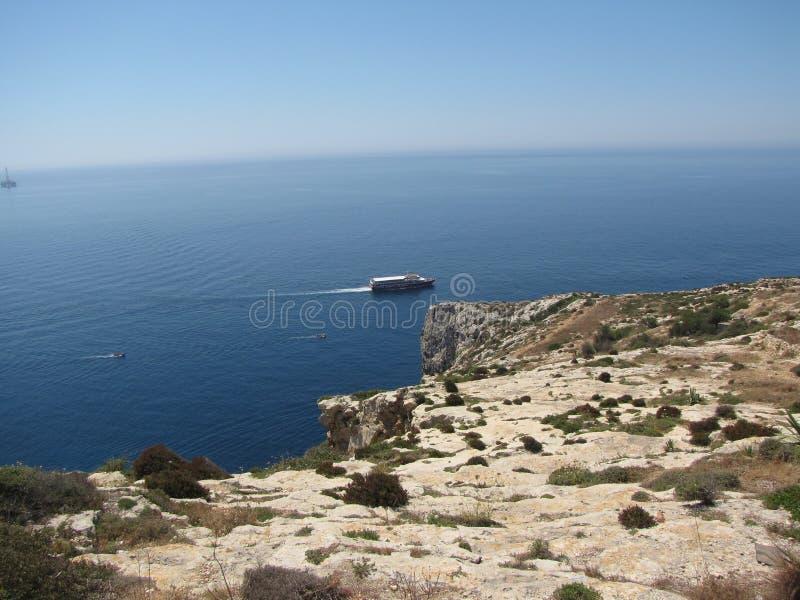 Malta - łódź krzyżuje wyspę blisko błękitnej groty zdjęcia stock