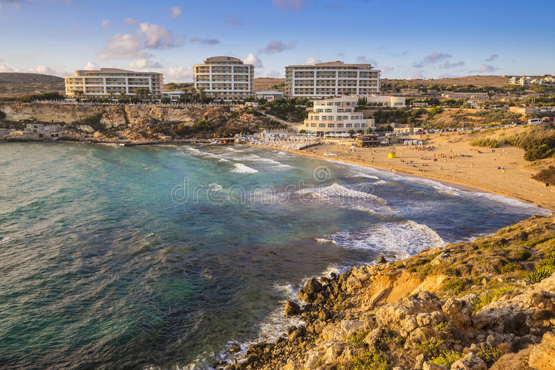 Malta - bahía de oro, ` s de Malta la mayoría de la playa arenosa hermosa en la puesta del sol fotos de archivo
