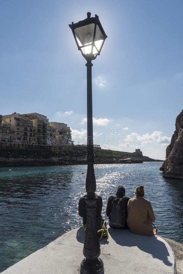 Sun Worship and lamp post on the jetty in Xlendi stock images