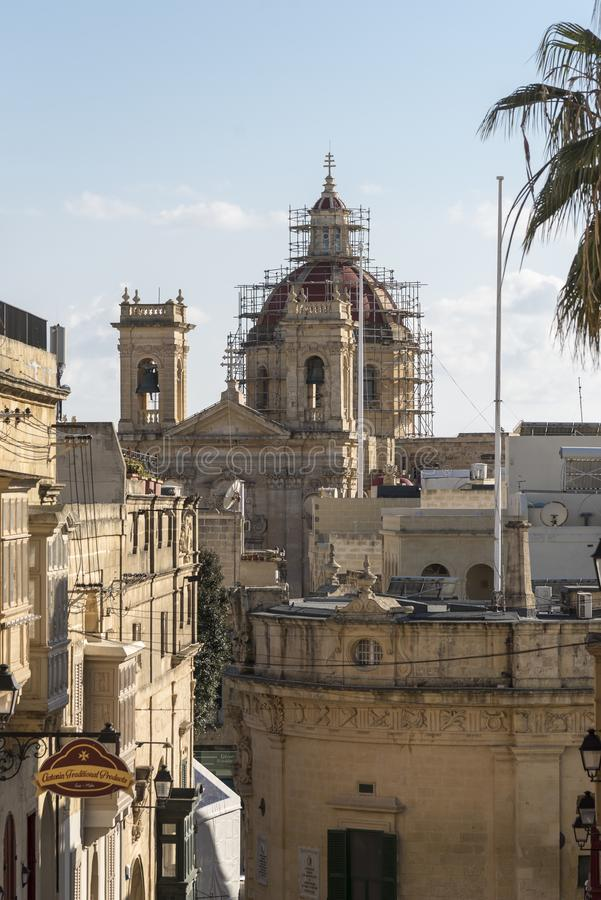Street down from the Citadel Victoria Gozo. The dome of St George`s Basilica under repair, Victoria also known as Rabat is the capital of Gozo Island, in Malta stock images