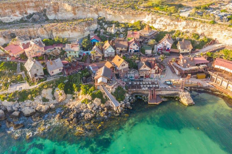 Malta Il-Mellieha Sikt av den Popeye för berömd berömd by den flyg- sikten och fjärden på ett solnedgångljus royaltyfria foton