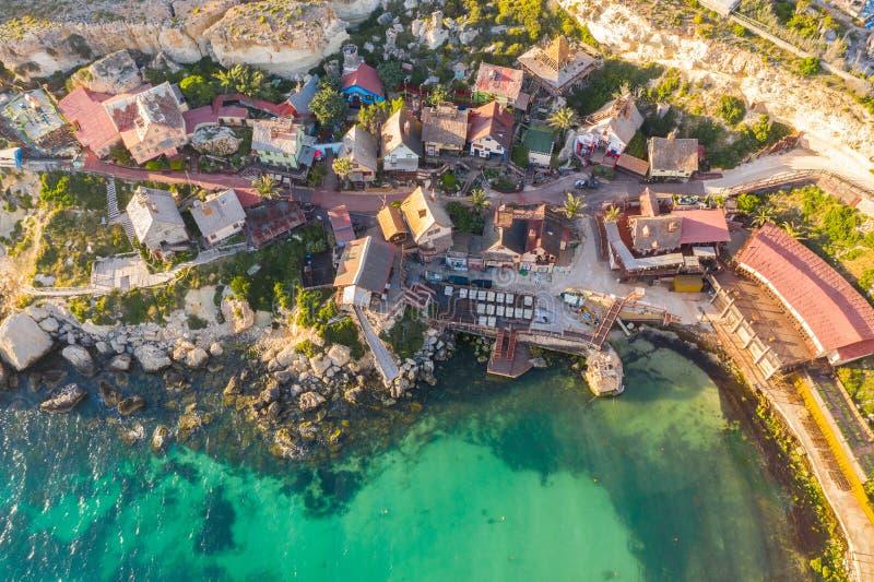 Malta Il-Mellieha Sikt av den Popeye f?r ber?md ber?md by den flyg- sikten och fj?rden p? ett solnedg?ngljus royaltyfri fotografi